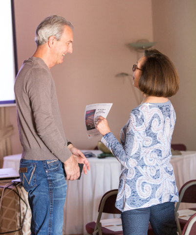 "Dr. Marc Baxter, left, talks with Sandee Tiberti prior to the start of his presentation of ""Happiness: How to Get More and Give More"" at the Stillpoint Center for Spiritual Devel ..."