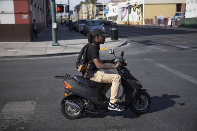 A scooter driver rides near Fremont Street and 7th Street on Tuesday, May 24, 2016, in Las Vegas. (Erik Verduzco/Las Vegas Review-Journal Follow @Erik_Verduzco)