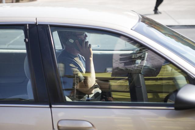 A motorist uses his phone while driving near Fremont Street and 7th Street on Tuesday, May 24, 2016, in Las Vegas. (Erik Verduzco/Las Vegas Review-Journal Follow @Erik_Verduzco)