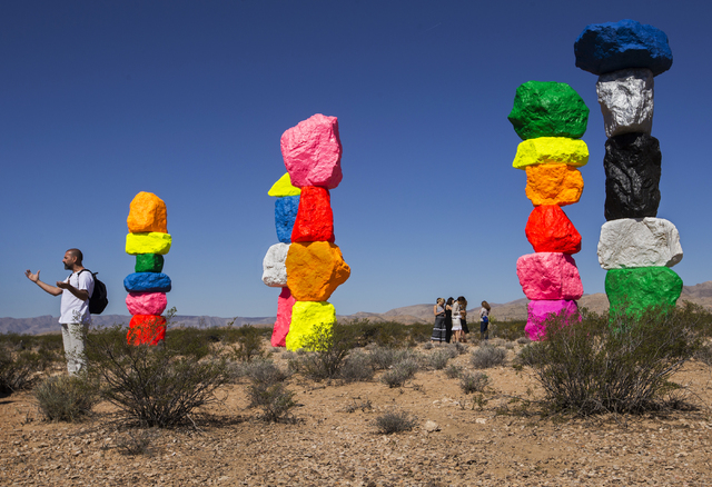 """Swiss artist Ugo Rondinone, right, visits the finished """"Seven Magic Mountains"""" installation, which has been in the works for years. Benjamin Hager/Las Vegas Review-Journal"""