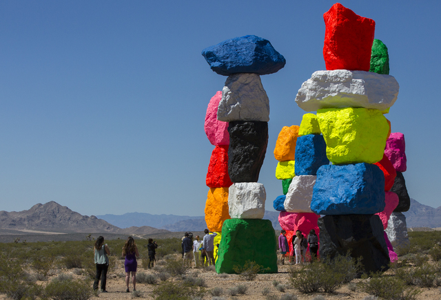"Swiss artist Ugo Rondinone, who wanted to ""introduce something artificial in a natural environment,"" unveils his ""Seven Magic Mountains"" project in the Jean dry lake bed Monday. Benjamin Hager/Las ..."