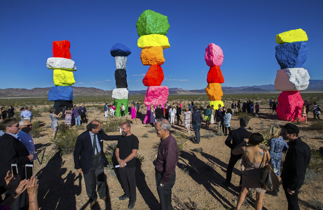 Swiss artist Ugo Rondinone, second from right, interacts with guests during the ribbon cutting ceremony for the Seven Magic Mountains art project, Monday, May 9, 2016, near Jean Dry Lake, Nevada.  ...
