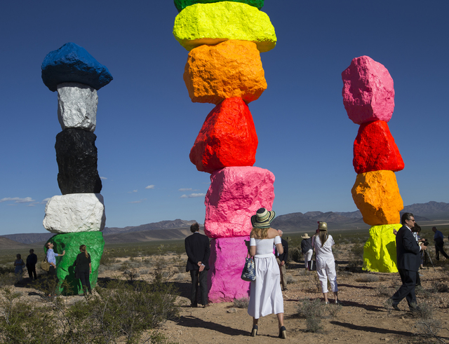 "Merlies Verhoeven, middle, admires the newly unveiled Seven Magic Mountains art project during the ribbon cutting ceremony, Monday, May 9, 2016, near Jean Dry Lake, Nevada. ""I'd seen it being work ..."