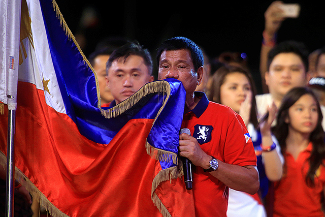 "Philippine presidential candidate and Davao city mayor Rodrigo 'Digong' Duterte kisses the Philippine flag during a ""Miting de Avance"" (last political campaign rally). (Romeo Ranoco/Reuters)"