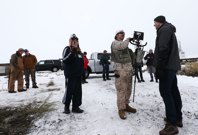Conservative radio host Pete Santilli, second from right, stands with others by the entrance to the Malheur National Wildlife Refuge headquarters near Burns, Ore., on Tuesday, Jan. 5, 2016. Chase  ...