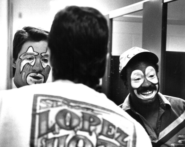 "Original caption, date unknown: ""Kevin Rich (left) and Leon Coffee apply make-up in mirrors."" (Ralph Fountain Photo)"
