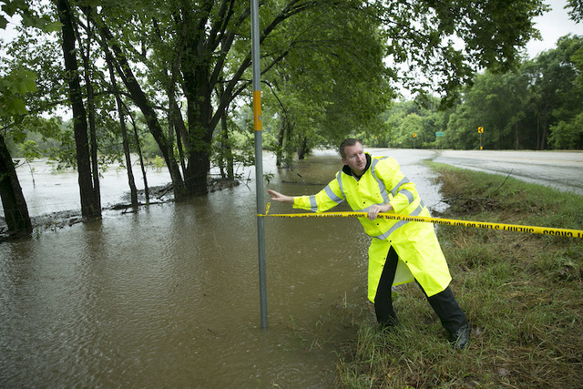 Bastrop County Sheriff Deputy John Deason closes FM 153 at River Bend Road, Friday, May 27, 2016, near Smithville, Texas, after flooding covered the road. (Jay Janner/Austin American-Statesman via AP)