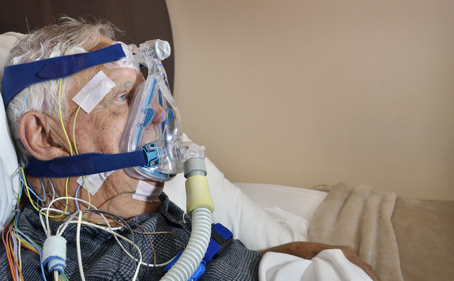 Ron Moroni uses a continuous positive airway pressure (CPAP) machine, which uses mild air pressure to keep airways open, while electrodes are connected to a monitoring, device during a sleep study ...
