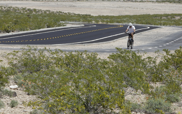 Dave Eckland of Henderson rides his bike on the first paved access road to Sloan Canyon National Conservation Area on Thursday, May 19, 2016. The BLM Thursday dedicated the road and other visitor  ...