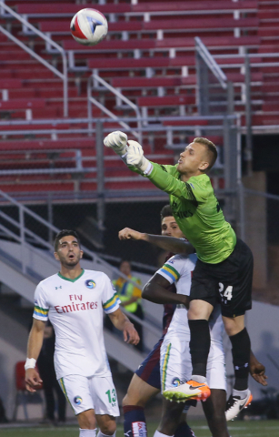 New York Cosmos goalie Brian Holt (24) punches a ball out of the box while defender Sebastian Guenzatti (13) looks on during a friendly between the New York Cosmos and SD Eibar, Wednesday, May 25, ...