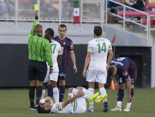 New York Cosmos' Sebastian Guenzatti (13) lays on the ground in pain as an SD Eibar defender is given a yellow card, Wednesday, May 25, 2016, at Sam Boyd Stadium in Las Vegas. Benjamin Hager/Las V ...