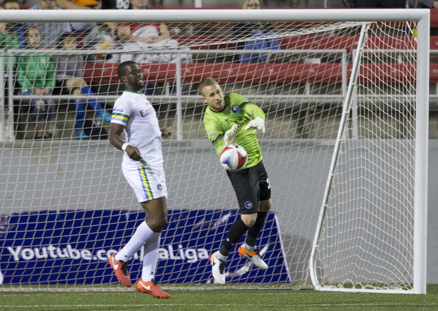 New York Cosmos goalie Brian Holt (24) grabs a loose ball while defender Kwame Watson-Siriboe (32) looks on during a friendly between the New York Cosmos and SD Eibar, Wednesday, May 25, 2016, at  ...