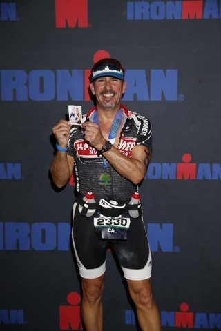 Cal Calderaro is shown after crossing the finish line of the Ironman Coeur d'Alene on June 29, 2014. He holds up a picture of his late daughter Jessica, who committed suicide. Special to View