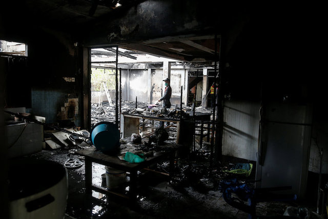 A forensic export inspects a burnt building at the Pitakkiat Wittaya School in the northern province of Chiang Rai, Thailand, May 23, 2016. (Athit Perawongmetha/Reuters)