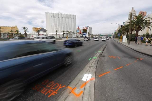 A car drives over paint left by investigators at the scene of an accident that left a pedestrian critically injured after they were hit by a car while crossing Tropicana Avenue at Ocean Drive in L ...