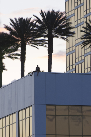 A man threatens to jump from Trump International in Las Vegas Friday, May 13, 2016. Las Vegas police have closed a portion of Fashion Show Drive, on the South side of the tower. ( Jason Ogulnik/La ...