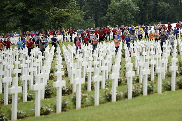French and German youths take part in a show at the French National cemetery outside the Douaumont Ossuary, in Douaumont, northeastern France, Sunday May 29, 2016, during a remembrance ceremony to ...