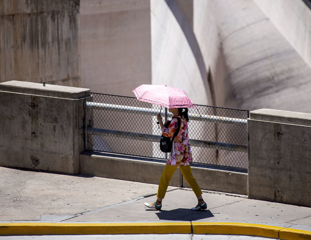 A woman carries an umbrella while walking past the Arizona Spillway at Hoover Dam on Monday, May, 31, 2016. Lake Mead area will be hitting in the 100's through out the week. Jeff Scheid/Las Vegas  ...