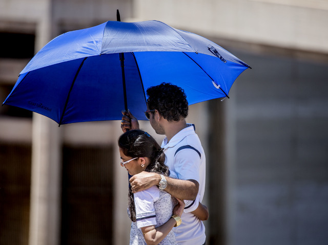 A couple walks with an umbrella while walking past the Arizona Spillway at Hoover Dam on Monday, May, 31, 2016. Lake Mead area will be hitting in the 100's through out the week. Jeff Scheid/Las Ve ...