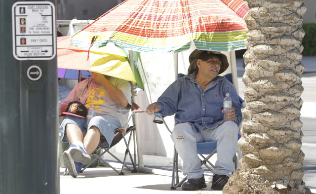 Daniel Avina, left, and Neptali Armenta protect themselves from sun as they protest what they say are unfair labor practice at the future Eclipse Theatre construction site at the corner of Casino  ...
