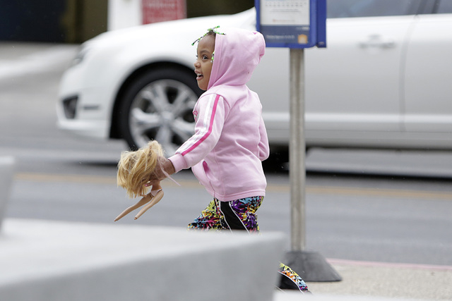 Bella Johnson, 4, holding her doll, runs against a strong wind to catch up with her mother on 3rd Street as the rain moves into the valley on Tuesday, May 17, 2016. Bizuayehu Tesfaye/Las Vegas Rev ...