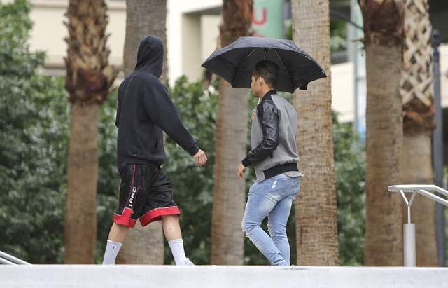A man holds his umbrella to protect himself from rain in front of the Regional Justice Cenetr as the rain moves into the valley on Tuesday, May 17, 2016. Bizuayehu Tesfaye/Las Vegas Review-Journal ...