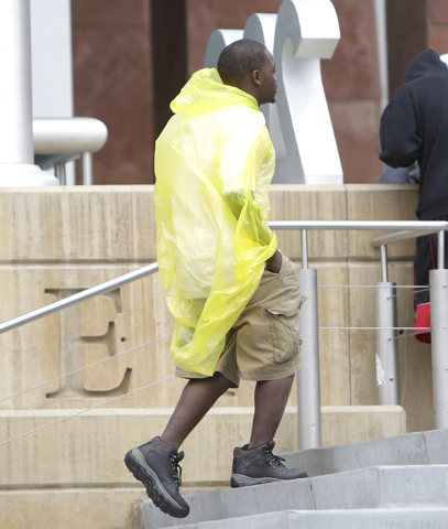A man protects himself from the rain with plastic bag as he enters the Regional Justice Center on Tuesday, May 17, 2016. Bizuayehu Tesfaye/Las Vegas Review-Journal Follow @bizutesfaye