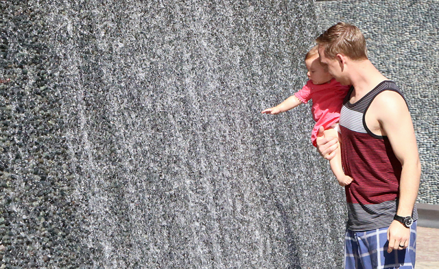 Micah Puhse watches as his 10-month-old daughter, Anastasia, both of Murrieta, Calif., cools herself at the water wall at The Park near T-Mobile Arena on the Las Vegas Strip on Tuesday, May 31, 20 ...