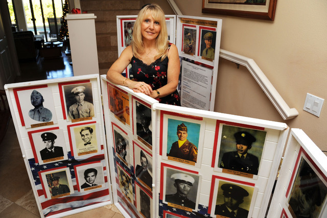 Janna Hoehn poses with photos of fallen Vietnam veterans at her Maui home Dec. 22, 2011. Hoehn is working with other volunteers who are trying to collect photos of the over 58,000 dead from the Vi ...