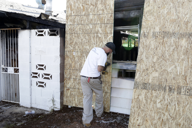 Joshua Vega of Westside Restoration boards up fire-damaged homes on 5138 and 5128 Wilbur St. on Tuesday, May 31, 2016. One person was displaced after a fire damaged two neighboring homes near McCa ...