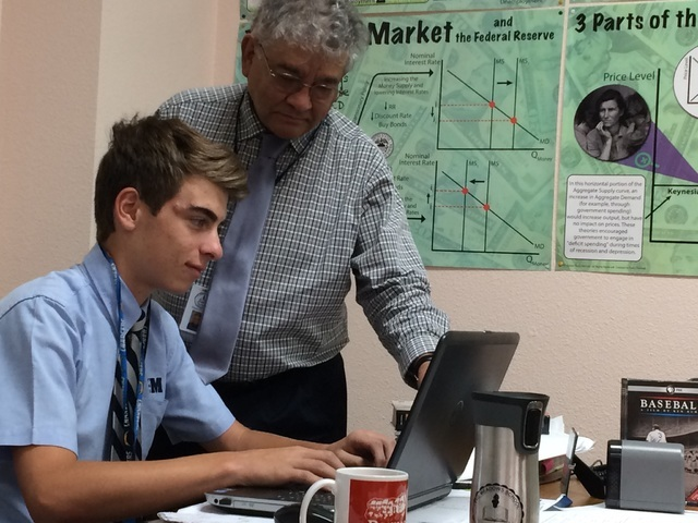 Dr. Miguel Enriquez, a teacher at The Meadows School, points out a notation on a stock trading site May 16, 2016, to student Blake Wynn, 16, who won $300, money put up by Enriquez to make his Intr ...