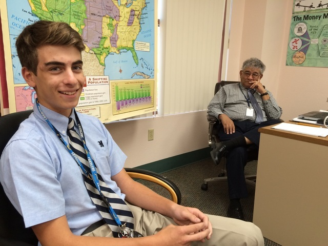 Blake Wynn, 16 and a sophomore at The Meadows School, talks about making stock trades as his Introduction to Economics instructor, Dr. Miguel Enriquez, listens May 16, 2016. Jan Hogan/View