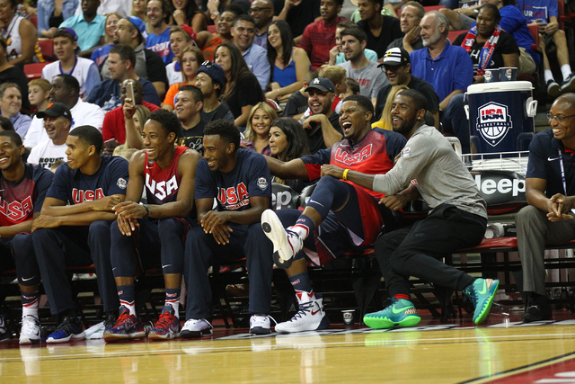 Players on the USA Blue team bench share a laugh with Kyrie Irving, far right, who was not playing, during the USA Basketball Showcase game at the Thomas & Mack Center in Las Vegas on Thursday ...