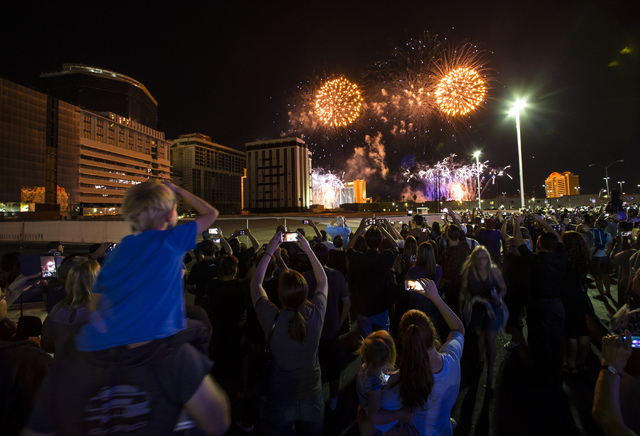 People watch fireworks before the implosion of the Monaco tower at the Riviera Hotel & Casino from the parking lot of the Peppermill in Las Vegas on Tuesday, June 14, 2016. CREDIT: Chase Steve ...
