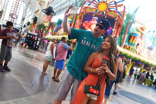 Tourists take a photo in front of Mermaids Casino at the Fremont Street Experience Saturday, June 25, 2016. Mermaids Casino, La Bayou and Glitter Gulch will close their doors on June 27th to make  ...