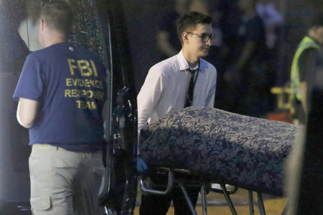 Police forensic investigators work at the crime scene of a mass shooting, as bodies are removed at the Pulse gay night club in Orlando, Florida, U.S. June 12, 2016.   (Jim Young/Reuters)