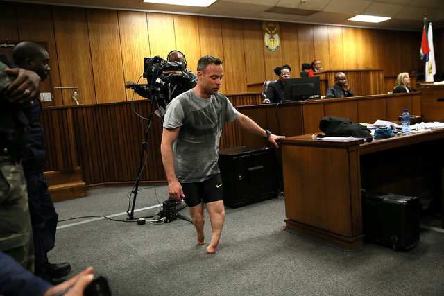 Paralympic gold medalist Oscar Pistorius walks across the courtroom without his prosthetic legs during the third day of his resentencing hearing for the 2013 murder of his girlfriend Reeva Steenka ...