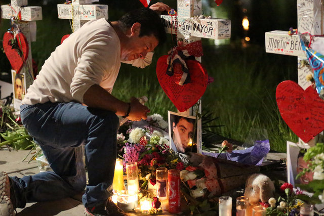 Jose Louis Morales cries on his knees at his brother Edward Sotomayor Jr.'s cross, that is part of a makeshift memorial for the victims of the Pulse night club shootings in Orlando, Florida, U.S., ...