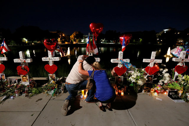 Jose Louis Morales cries on his knees as he is hugged by a woman at his brother Edward Sotomayor Jr.'s cross, that is part of a makeshift memorial for the victims of the Pulse night club shootings ...
