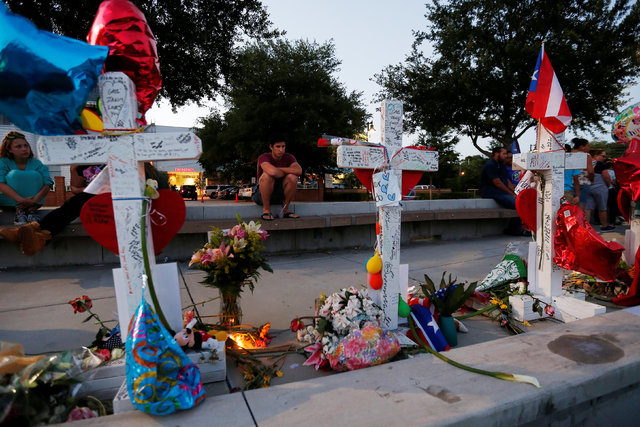 A man sits and looks at a row of crosses that make up part of a makeshift memorial for the victims of the Pulse night club shootings in Orlando, Florida, U.S., June 20, 2016.  REUTERS/Carlo Allegri