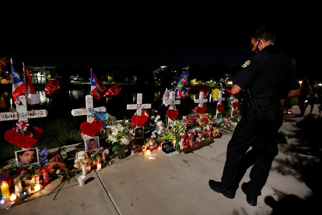 A police officer looks at a row of crosses that make up part of a makeshift memorial for the victims of the Pulse night club shootings in Orlando, Florida, U.S., June 20, 2016.  REUTERS/Carlo Allegri