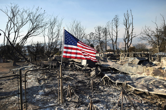 An American flag flies above wreckage at a residence leveled by the Erskine Fire in South Lake, California, June 26, 2016. (Noah Berger/Reuters)