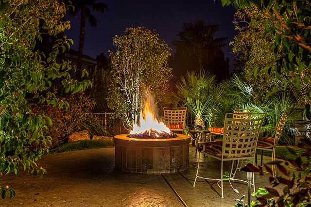 A large fire pit is a centerpiece in a gathering area. (COURTESY OF LUXURY ESTATES INTERNATIONAL)