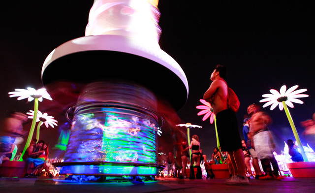 Attendees watch as others spin around the Caterpillar's Garden art installation at Electric Daisy Carnival at the Las Vegas Motor Speedway in Las Vegas on Saturday, June 20, 2015. (Chase Stevens/L ...