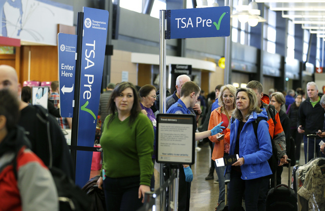 Travelers authorized to use the TSA PreCheck expedited security line at Seattle-Tacoma International Airport in Seattle have their documents checked by Transportation Security Administration worke ...