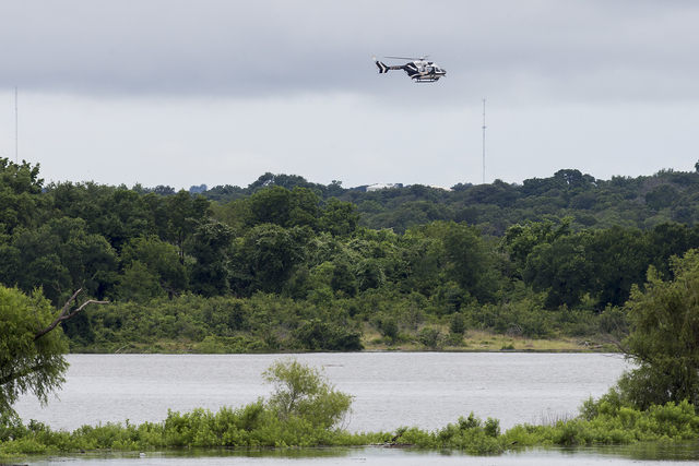 A Texas DPS helicopter flies over Lake Belton near the scene of an accident at Fort Hood at Owl Creek Park near Gatesville, Texas, on Thursday, June 2, 2016. Fort Hood says several soldiers are de ...