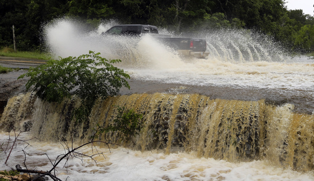 A motorist passes through a low-water crossing on a road closed due to high water near New Braunfels, Texas, Thursday, June 2, 2016. About half of Texas is under flood watches or warnings, includi ...