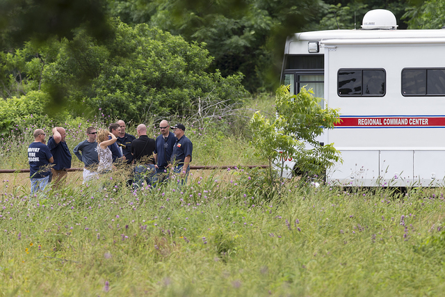 Emergency responders talk near the scene of an accident at Fort Hood at Owl Creek Park near Gatesville, Texas, on Thursday, June 2, 2016. Fort Hood says several soldiers are dead and six are missi ...