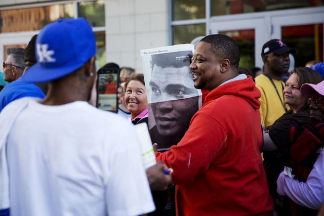 Members of the public stand in line with a newspaper image of Muhammad Ali while waiting for the box office to open for tickets to Ali's memorial service Friday at the KFC Yum! Center Wednesday, J ...