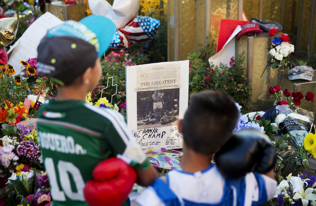 Joseph Garcia, 6, right, and Jafet Figueroa, 9, both of Louisville, look over a makeshift memorial to Muhammad Ali at the Muhammad Ali Center on Tuesday, June 7, 2016, in Louisville, Ky. (David Go ...